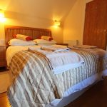 Main bedroom with king size bed, oak beams and floor